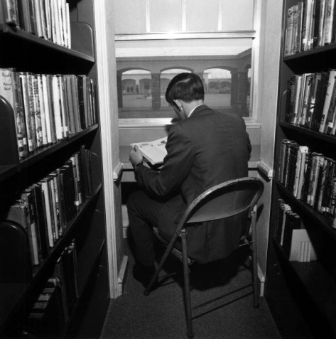 man sitting in library stacks reading a book