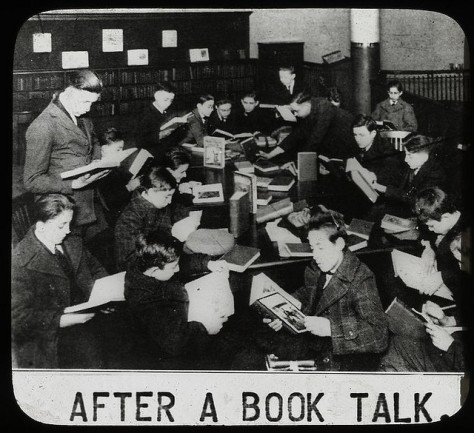 black and white photo of boys reading books in an old library