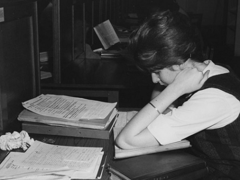 white woman with sixties hair studying from notes and a binder