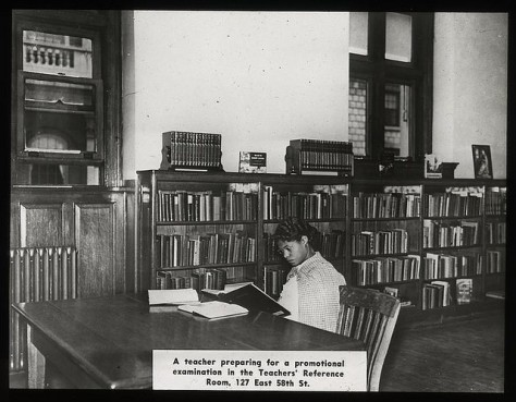 young black woman in sixties clothes studying at a library table